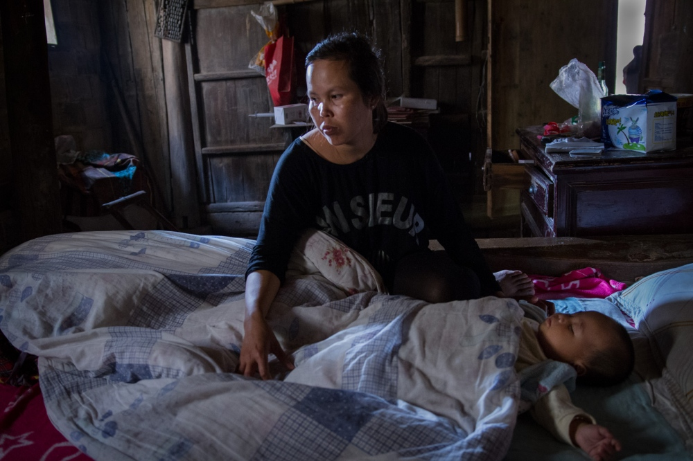 Buntha sits in bed next to the sleeping baby in the early morning, June 2015. She has to take care of the baby and housework mostly on her own because her husband works long hours.