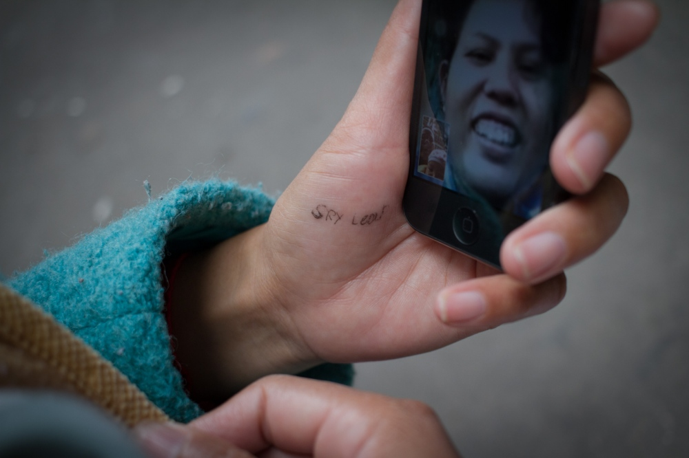 Buntha video-chats with her sister Srey Leap, who's in Cambodia through a smartphone app. She wrote down her sister's caller ID on her hand, February 2015. International phone calls are expensive in China, but the internet connection is good enough for audio or video-chatting.