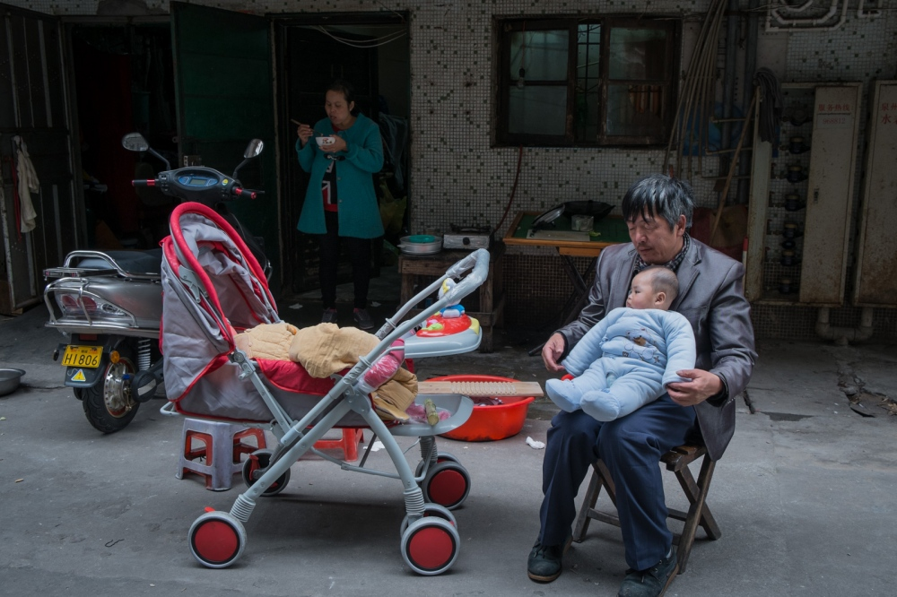 Buntha's husband Zou plays with the baby in the empty space in front of their room while Buntha is having lunch, March 2015.