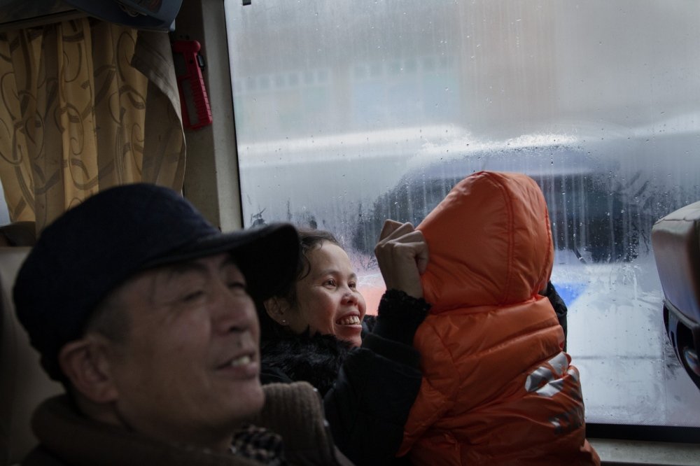 Buntha and Zou take their son to visit Zou's family by bus before the Chinese New Year, January 2016.