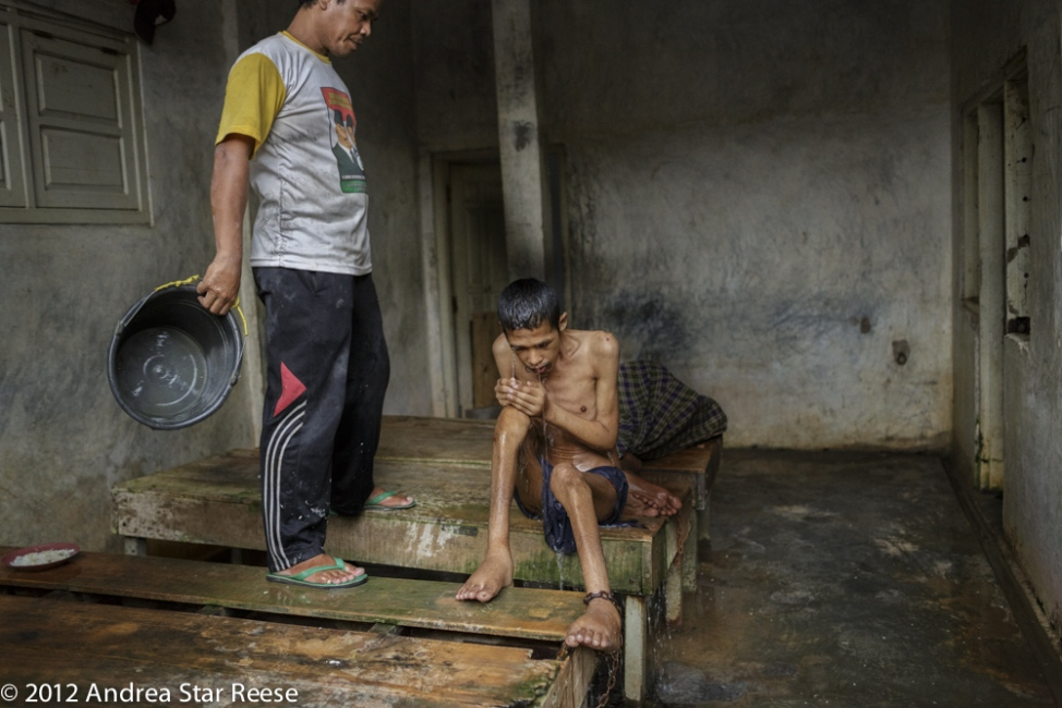 "Mustafa, the sole assistant at Syamsul Ma' arif family shelter ""gives Akrom a shower"". After living at the center for a year his ankles and feet were swelling and his rib cage was visible. One year later in 2013 Akrom died after receiving a shower."