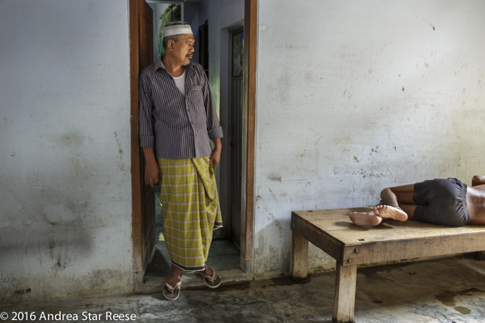 Syamsul Ma'arif stands in the door way that separates his residence from the shelter. Kyai Syamsul admits that he does not know how to help many of the men and women under his care. He is only able to give the method of treatment he learned from his father.