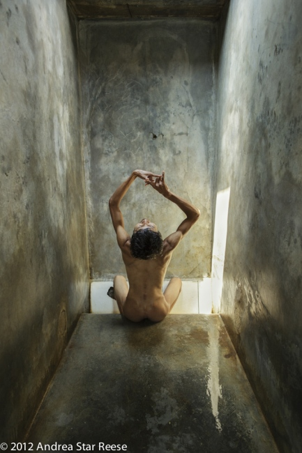 Agus sings in his cage, his hands moving in an intricate dance at Pengobatan Alternatif Jasono. His feet are in a gutter filled with water that he uses when he is thirsty.