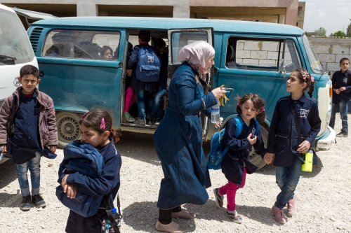 A teacher of the Saadnayel School guides students to their buses as they finish the morning class. Transportation is organized to bring children back to their parents. Refugees settlements are scattered across the border region.
