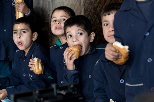 Children are eating sandwiches during the morning break at Saadnayel School. The school ensures that every child get one meal per day. Some Non-Formal Education programs also include child protection services and nutritional assistance.
