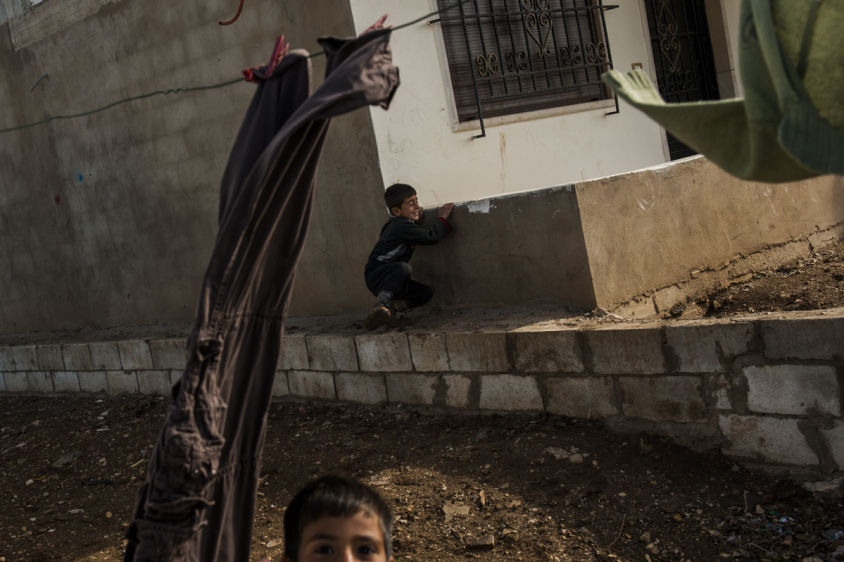 Two children, Syrian refugees, play behind an abandoned building in The Bekaa Valley, Lebanon on March 10, 2014.