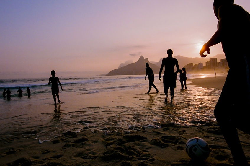 A group of boys juggle a soccer ball on Ipanema beach at sunset, in Rio de Janeiro, Brazil. August 2013.