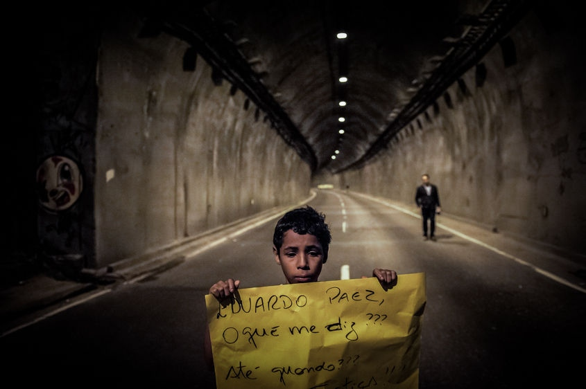 A boy holds a sign in front of a blocked tunnel during a protest to press for clarifications on missing persons including a bricklayer who recently disappeared, in Rio de Janeiro, Brazil, Thursday, Aug. 1, 2013. The 42-year-old father of six was picked up for police questioning on suspicions of involvement in drug trafficking, but was released shortly thereafter. He has not been seen from since. Official statistics showing that nearly 35,000 people were reported as missing in Rio state alone over the past five years.