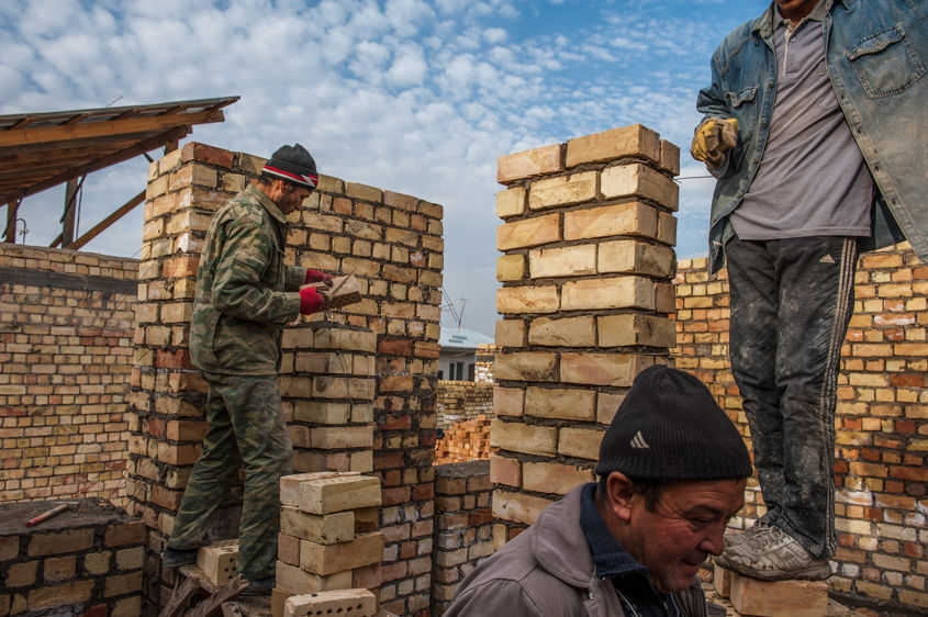Three men, neighbors, work together to lay brick while rebuilding the foundation for a new home in the Sulaiman-Too mahallah in Osh, Kyrgyzstan Nov. 5, 2011.