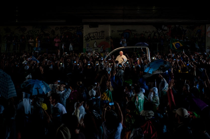 People greet Pope Francis as he travels through a road tunnel in his pope-mobile in Rio de Janeiro, Brazil, early Saturday, July 27, 2013. Pope Francis on Saturday challenged bishops from around the world to get out of their churches and preach, and to have the courage to go to the farthest margins of society to find the faithful.