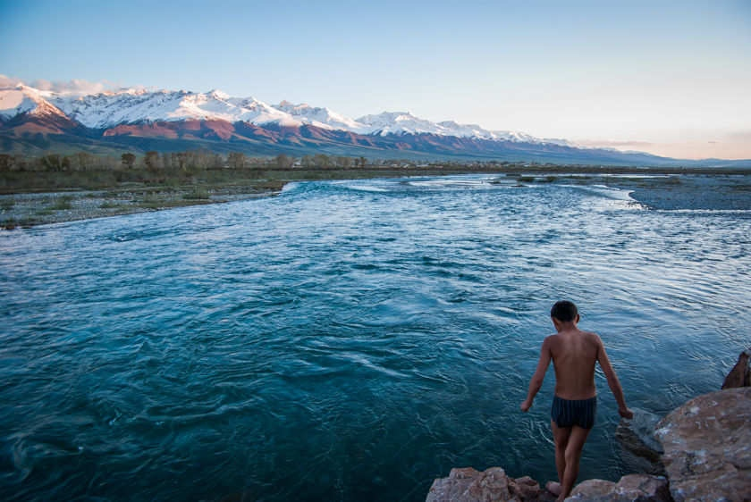 A teenager in At-Bashy village, Kyrgyzstan, readies himself for a plunge into the first flows of a spring thaw in a stream at the base of the Tian Shan Mountains bordering western China on May 13, 2009.
