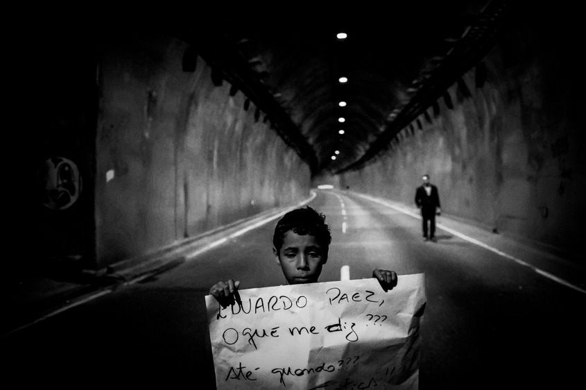 A boy holds a sign in front of a blocked tunnel during a protest to press for clarifications on missing persons including a bricklayer, who recently disappeared, in Rio de Janeiro, Brazil, Thursday, Aug. 1, 2013. The 42-year-old father of six was picked up for police questioning on suspicions of involvement in drug trafficking, but was released shortly thereafter. He has not been seen from since. Official statistics showing that nearly 35,000 people were reported as missing in Rio state alone over the past five years.