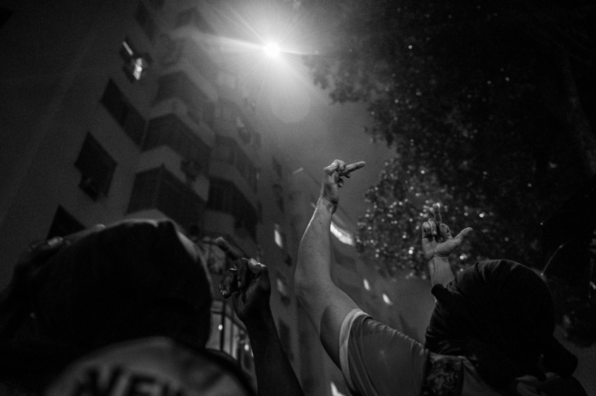 Protestors hold up their middle fingers at a police helicopter shining a spotlight on them from above. Rio de Janeiro, Brazil. July 2013.