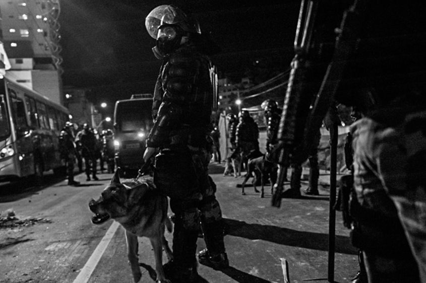 A police officers uses a canine to control the flow of protestors to an area. In Rio de Janeiro, Brazil in June 2013.