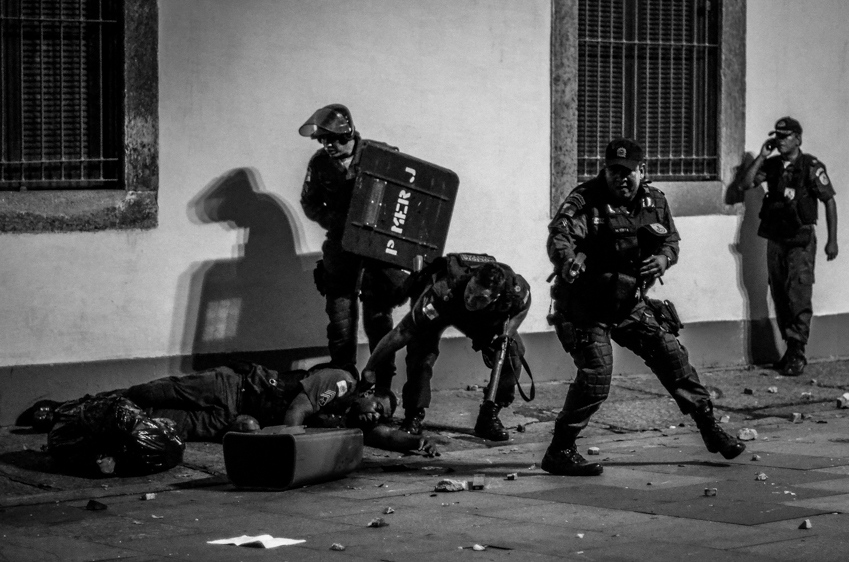 A police officer, second from right, holds an electroshock gun as another policeman is dragged by colleagues during clashes with demonstrators outside the state legislative assembly in Rio de Janeiro, Brazil, Monday, June 17, 2013. Officers in Rio fired tear gas and rubber bullets when a group of protesters invaded the state legislative assembly and threw rocks and flares at police. Protesters massed in at least seven Brazilian cities Monday for another round of demonstrations voicing disgruntlement about life in the country, raising questions about security during big events like the current Confederations Cup and a papal visit next month.