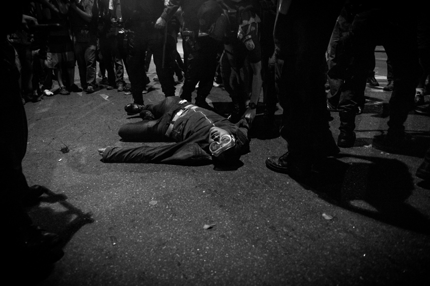 A man lays unconscious after police confronted protestors who had gathered near the Guanabara Palace in Rio de Janeiro, Brazil, Monday July 22, 2013. Police and anti-government protesters clashed outside the palace hosting Pope Francis welcoming ceremony. About an hour after the pope concluded his short speech, police began cracking down on the protests, firing rubber bullets and tear gas in an effort to disperse the crowd.