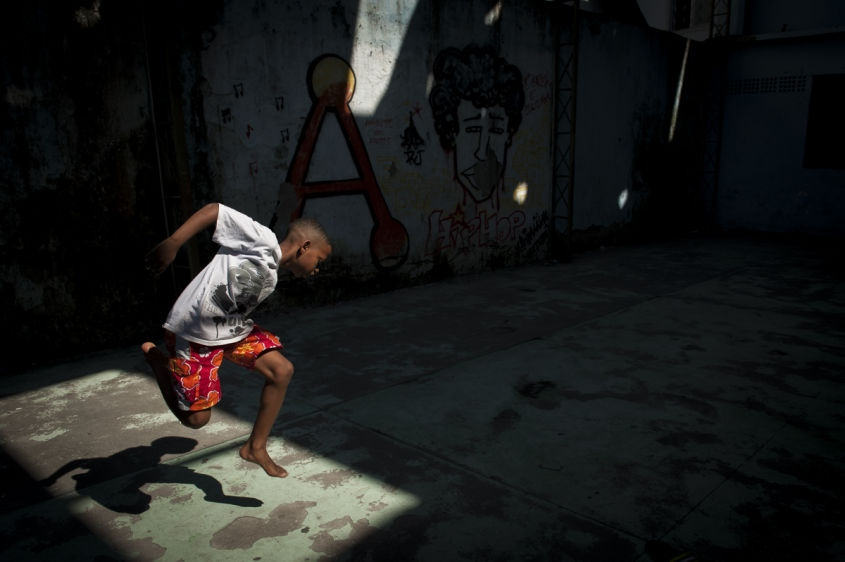 "In this Aug. 3, 2013 photo, a boy jumps in the air and grabs his foot while practicing a step from a dance form called ""passinho,"" or ""little step,"" at a makeshift dance studio in the Borel favela, in Rio de Janeiro, Brazil. Passinho is a mix of samba-esque footwork, breakdance handstands, free spins and athletic acrobatics, all set to a music heavy on funk hooks laid over snare beats."