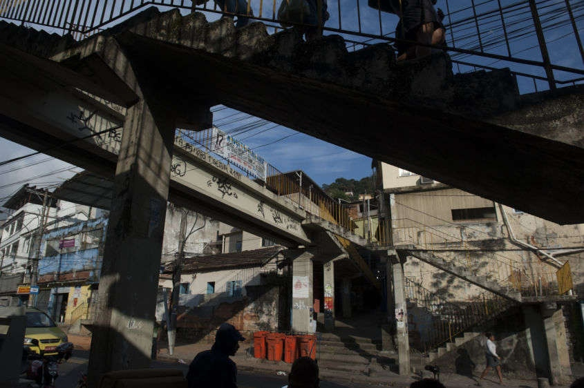 "In this Aug. 14, 2013 photo, pedestrians walk in the Borel favela, in Rio de Janeiro, Brazil. In slums that have undergone police ""pacification,"" with officers pushing out gangs and setting up permanent posts, a dance form called ""passinho,"" or ""little step,"" has sprung up to replace the more raucous ""baile funk"" gatherings."
