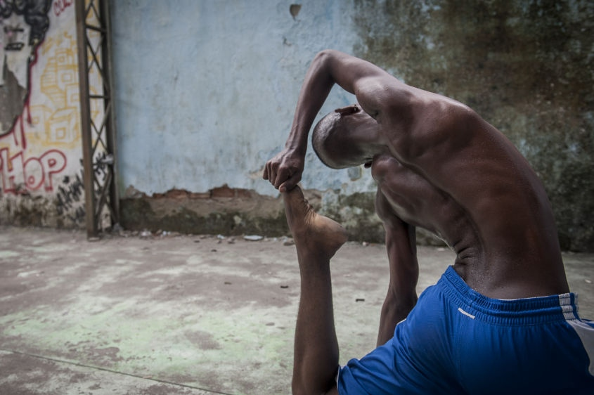 "In this Aug. 17, 2013 photo, Hilton Santos da Cruz Jr. practices during a ""passinho,"" or ""little step,"" session at a makeshift dance studio in the Borel favela, Rio de Janeiro, Brazil. The dance's popularity has benefited from a police crackdown on another late night activity, more raucous ""baile funk"" parties often organized by criminal gangs. In passinho gatherings, participants watch as performers square off against each other in choreographed duels. The dance's new superstars include Cruz, known as ""Hiltinho Fantastico"" or Fantastic Little Hilton."