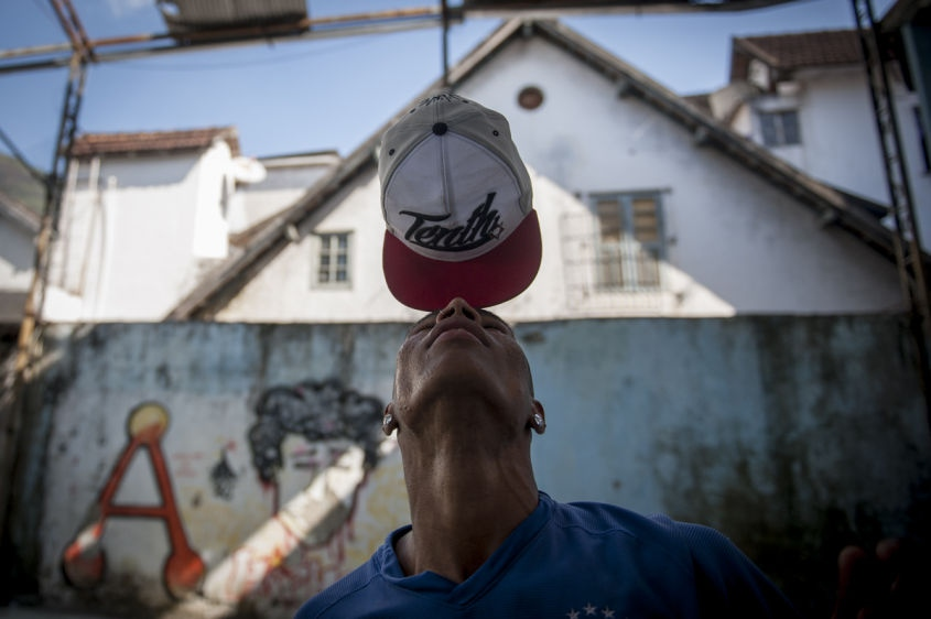 "In this Aug. 10, 2013 photo, a young man balances his cap on his nose, a common ""passinho,"" or ""little step"" move in front of friends at a makeshift dance studio in the Borel favela, in Rio de Janeiro, Brazil. Passinho is a free-form style of dance that is catching on with young people all over the city. The dance borrows from various influences, including samba movements, break dance handstands, and is set to pounding beats on top of soulful hooks."
