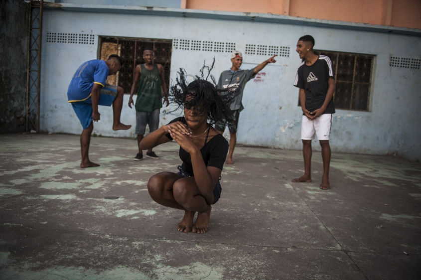 "In this Aug. 10, 2013 photo, Marcelly de Mello da Silva, 15, practices her ""passinho,"" or ""little step,"" moves at a makeshift dance studio in the Borel favela, in Rio de Janeiro, Brazil. Passinho is a free-form style of dance that is catching on with young people all over the city. The dance borrows from various influences, including samba movements, break dance handstands, and is set to pounding beats on top of soulful hooks. Although Passinho has been around for years, it only recently gained momentum after the baile funk, preferred by drug traffickers, started disappearing during the pacification of the slums."