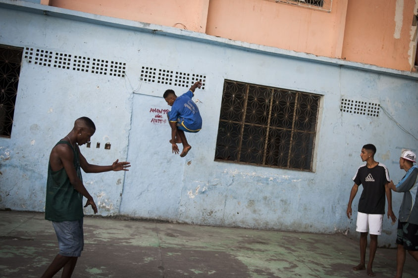 "In this Aug. 10, 2013 photo, Hilton Santos da Cruz Jr, left, practices his hand movements while a friend springs off a wall during a ""passinho,"" or ""little step,"" session at a makeshift dance studio in the Borel favela, Rio de Janeiro, Brazil. The dance's popularity has benefited from a police crackdown on another late night activity, ""baile funk"" parties often organized by criminal gangs. In passinho gatherings, participants watch as performers square off against each other in choreographed duels, while the baile funk parties tend to attract hundreds of revelers dancing in close contact."