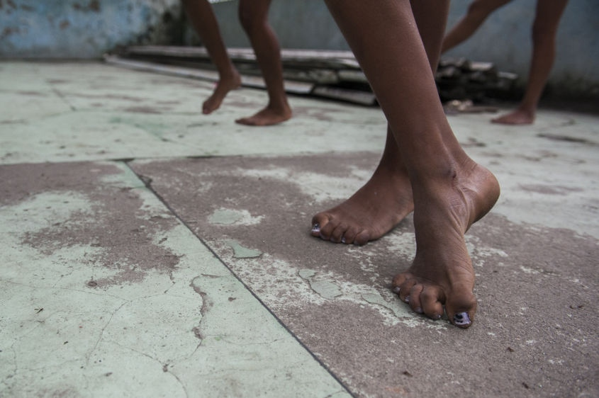 "In this Aug. 17, 2013 photo, Marcelly de Mello da Silva, 15, leads a ""passinho,"" or ""little step,"" instruction session at a makeshift dance studio in the Borel favela, in Rio de Janeiro, Brazil. Passinho is a free-form style of dance that is catching on with young people all over the city. The dance borrows from various influences, including samba movements, break dance handstands, and is set to pounding beats on top of soulful hooks. Although Passinho has been around for years, it only recently gained momentum after the baile funk, preferred by drug traffickers, started disappearing during the pacification of the slums."