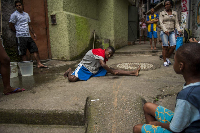 "In this Aug. 17, 2013 photo, sixteen-year-old Hilton Santos da Cruz Jr., shows off his ""passinho,"" or ""little step,"" moves in front of friends in a small plaza in the Borel favela, in Rio de Janeiro, Brazil. Passinho has been around for years, but it recently began spreading through social media, with dancers posting videos of their moves on YouTube and Facebook, sometimes drawing thousands of followers. The dance's new superstars include Cruz, known as ""Hiltinho Fantastico"" or Fantastic Little Hilton."