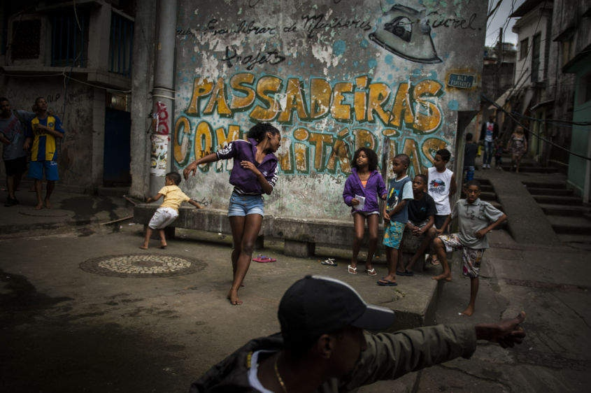 "In this Aug. 17, 2013 photo, Marcelly de Mello da Silva, 15, shows off her ""passinho,"" or ""little step,"" moves to a young audience gathered in the Borel favela, in Rio de Janeiro, Brazil. Passinho is a free-form style of dance that is catching on with young people all over the city. The dance borrows from various influences, including samba movements, break dance handstands, and is set to pounding beats on top of soulful hooks. Although Passinho has been around for years, it only recently gained momentum after the baile funk, preferred by drug traffickers, started disappearing during the pacification of the slums."