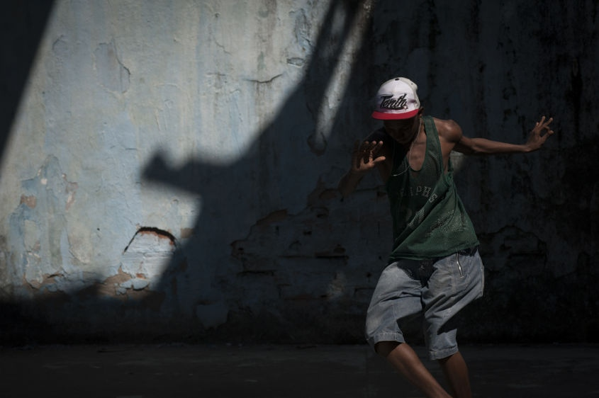 "In this Aug. 10, 2013 photo, sixteen-year-old Hilton Santos da Cruz Jr., dances ""passinho,"" or ""little step,"" in the Borel favela, in Rio de Janeiro, Brazil. Passinho is a free-form style of dance that is catching on with young people all over the city. The dance borrows from various influences, including samba movements, break dance handstands, and is set to pounding beats on top of soulful hooks."