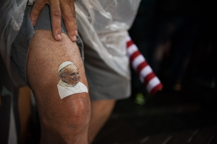 A man holds up the cuff of his shorts to show off his temporary tattoo of Pope Francis while waiting to get a glimpse of the pontiff making his way to the St. Francis of Assisi of the Providence of God Hospital, where the Franciscans look after alcohol and drug addicts, in Rio de Janeiro, Brazil, Wednesday, July 24, 2013.