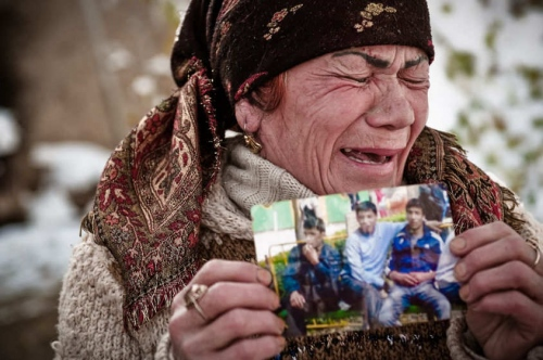 An Uzbek woman wails with grief while holding up a photo of her dead son (right), who was kidnapped and executed, to aid workers in Osh, Kyrgyztan on November 10, 2011.