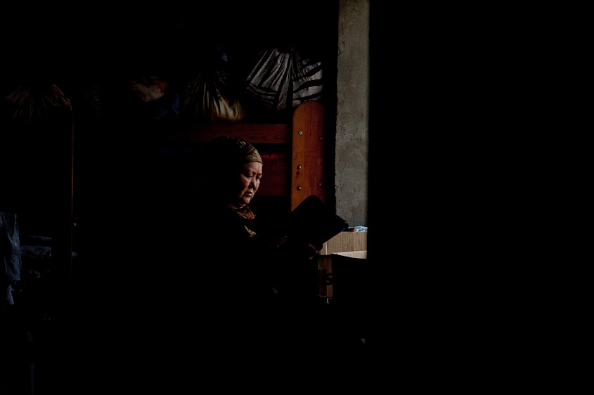 An uzbek woman searches for documents in her home in Osh, Kyrgyzstan in November 2011.