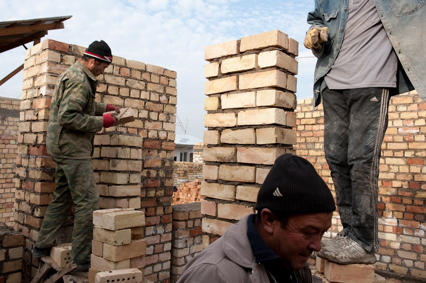 Two men lay brick, forming walls, while another carries more over to rebuild their house after it was destroyed in ethnic violence occurred in Osh, Kyrgyzstan in 2011. November 2010.