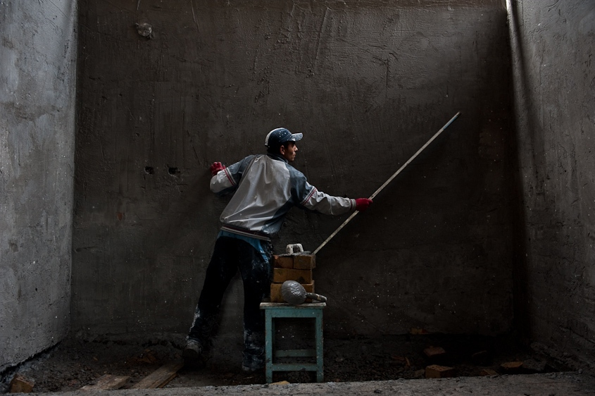 A boy with a level smooths out cement applied to the brick walls of a room in Osh, Kyrgyzstan in November, 2011.
