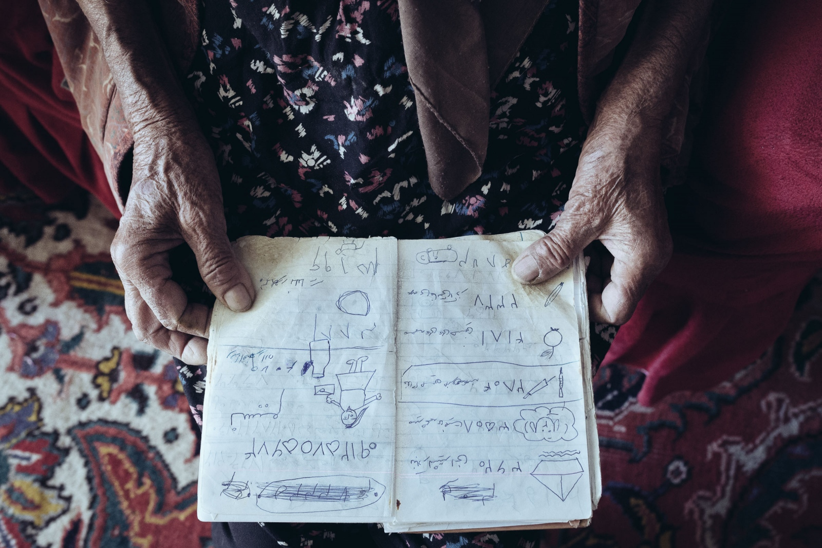 An elderly woman from the port.  She and her husband owned a motel on the coast. Since she is illiterate, she has marked emergency number with drawings according to the contacts' jobs. She drew a ship with waves to mark number for 3632 port shipping.   The phone book belongs to the past years when the lake and motel were thriving. Lake Urmia|East-Azerbaijan|Iran.2015