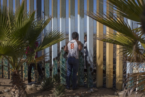 A man speaks to his family member (behind the wall in the United States) through the border fence in Playas de Tijuana, Mexico. For many, it is the only way that they can see their loved ones in person.