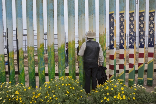 Jose Marquez poses for a photograph that a visitor is taking of his family on the other side of the border wall. Marques has not been able to hug his daughter Susana in 14 years, since he was deported from the United States after living and working in San diego for 18 years.