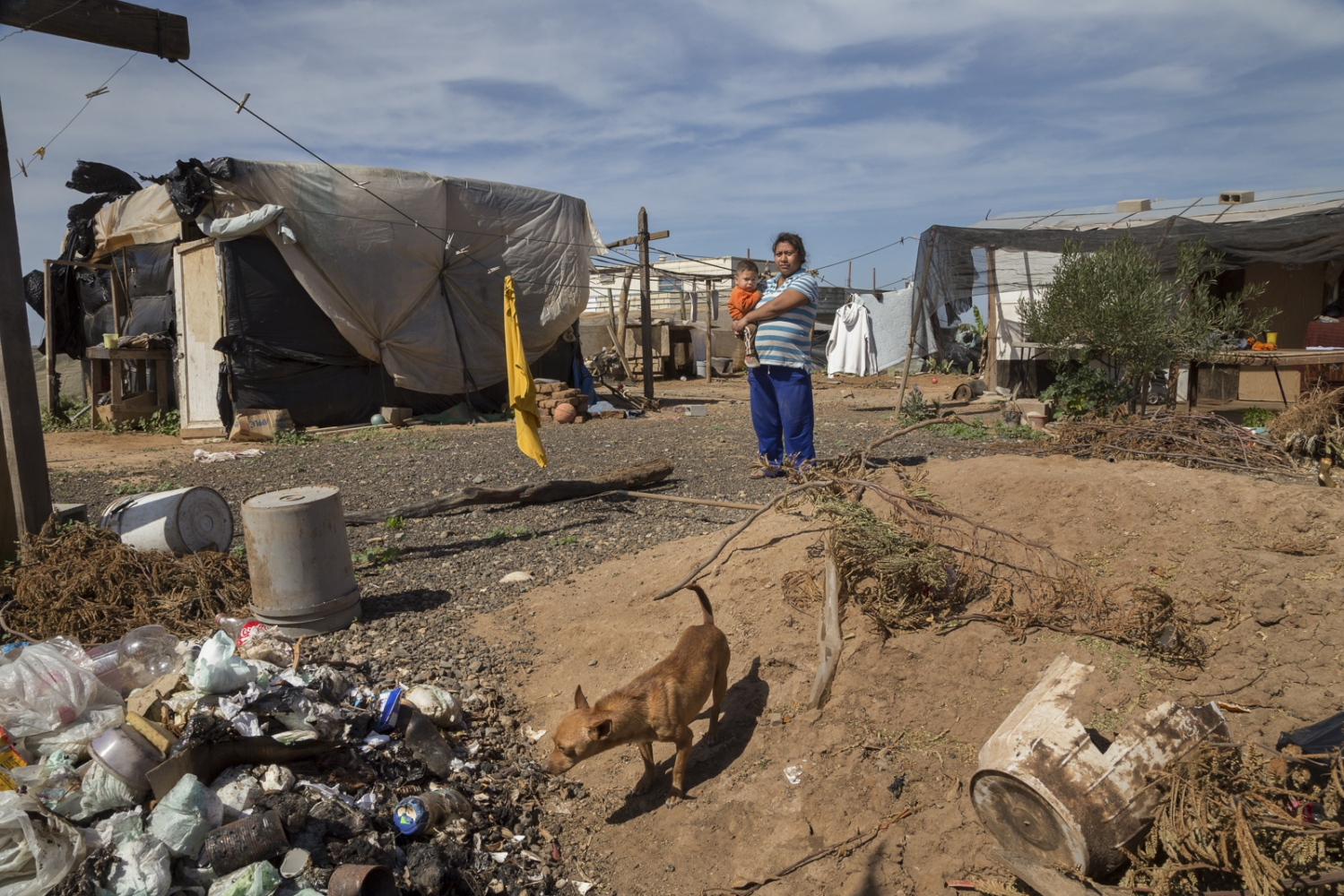 Aurora Ramirez, 20, and her son Mario Alberto, 18 months, stand in the yard next to their house made of plastic and cardboard. Farmworkers live in areas of difficult access where large families are crammed into small rooms in makeshift houses. They live without electricity or running water and their front yards are often full of dirt, trash and burnt garbage.