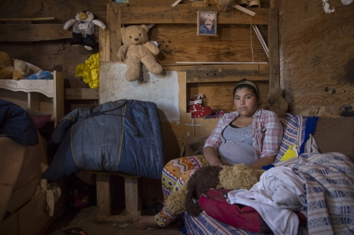 Cynthia Delgadillo, 14, sits in her room which is an add on to her mother's house, made mostly of scrap wood and covered in plastic. She shares it with her live in boyfriend who is 17 and works in the field.
