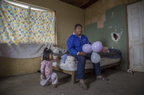 Felipe Ramirez sits in his bedroom with one of his granddaughters. Felipe works in the fields hadpicking strawberrys. He makes 10 dollars a day.