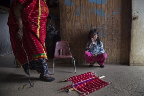 Azucena Bautista, 5, sits and waits for her grandmother Francisca who is getting ready to start looming in a traditional Oaxacan stile in their house in Mexico's San Quintin valley.