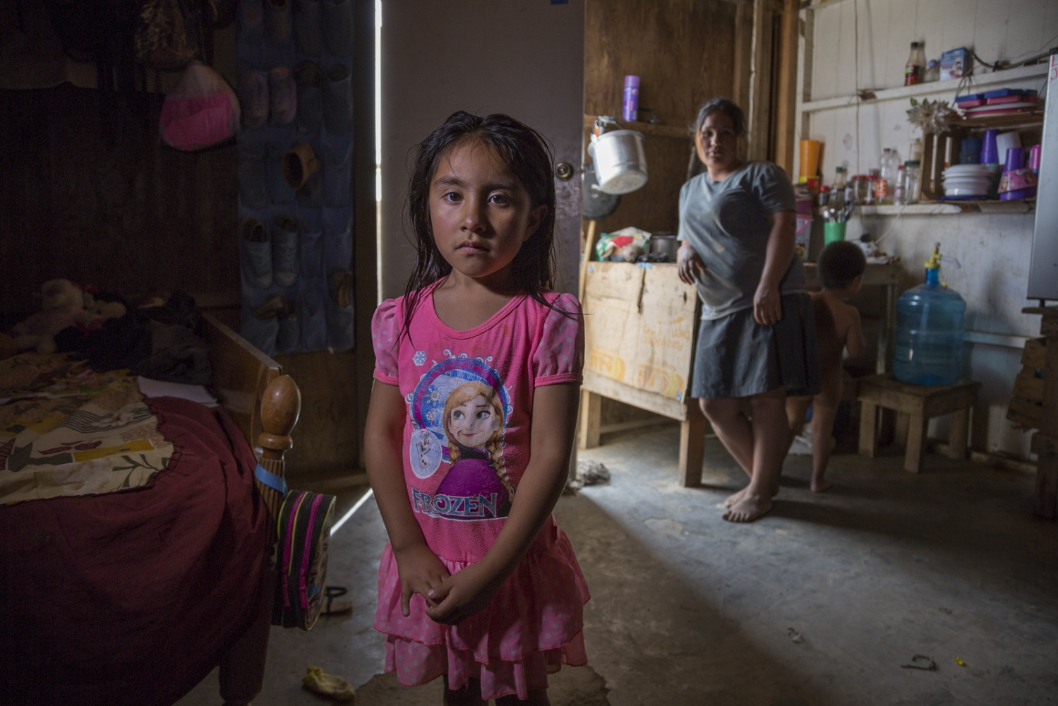 Six year-old Litzy stands with her mom Esmeralda and younger brother Jafet, 2 years old, inside their humble one-room house in Mexico's San Quintin valley. They live without running water and get electricity shared to them through a neighbor. Esmeralda's husband works in the field picking tomatoes and makes 150 pesos a day, approximately 8 US dollars.