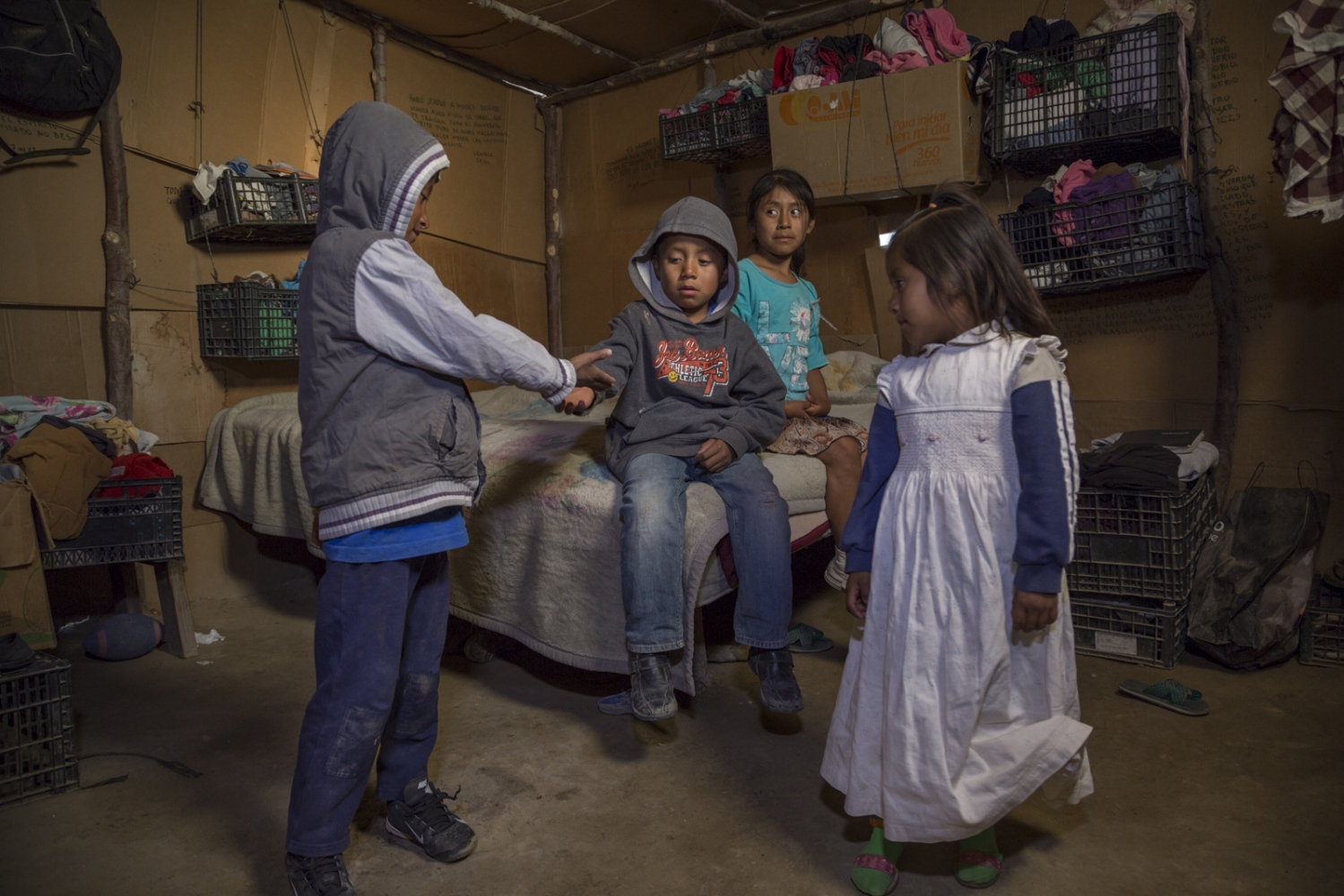 Siblings Juan Carlos, 6, Lizbeidy, 3, Luis Angel, 7, and Yolet, 9, play in their room of their house made of cardboard and plastic in the San Quintin valley in Mexico. Their parents work in the fields handpicking strawberries for 9 U.S dollars a day sometimes working more than 12 hours.