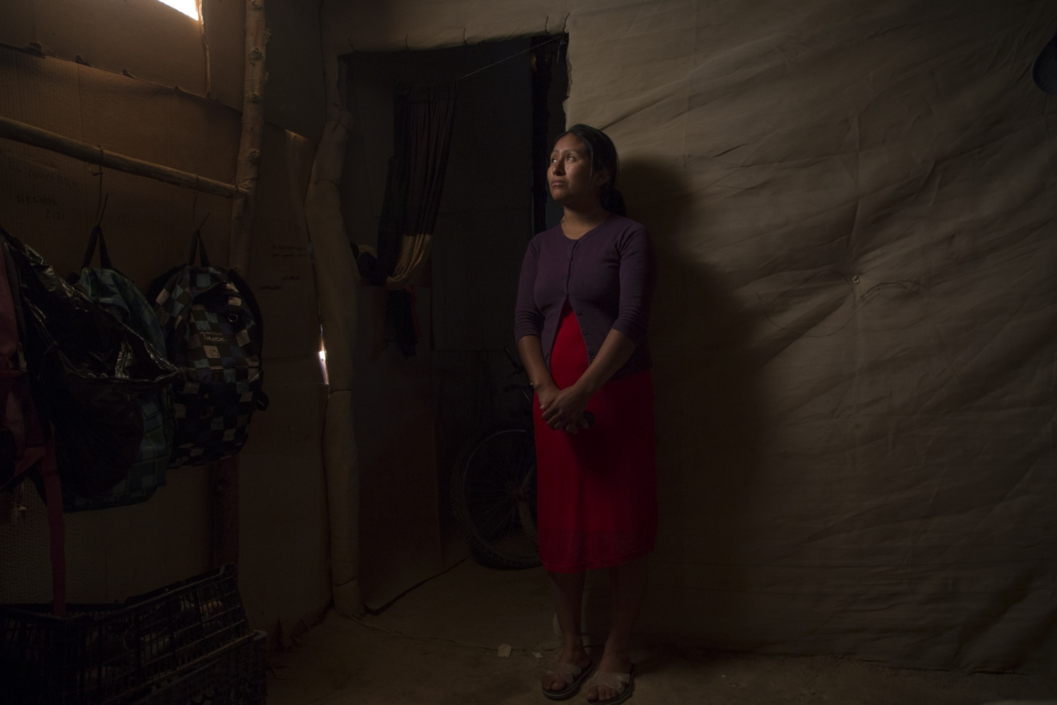 Isabel Policao inside of her humble house made of cardboard and plastic in Mexico's San Quintin valley.