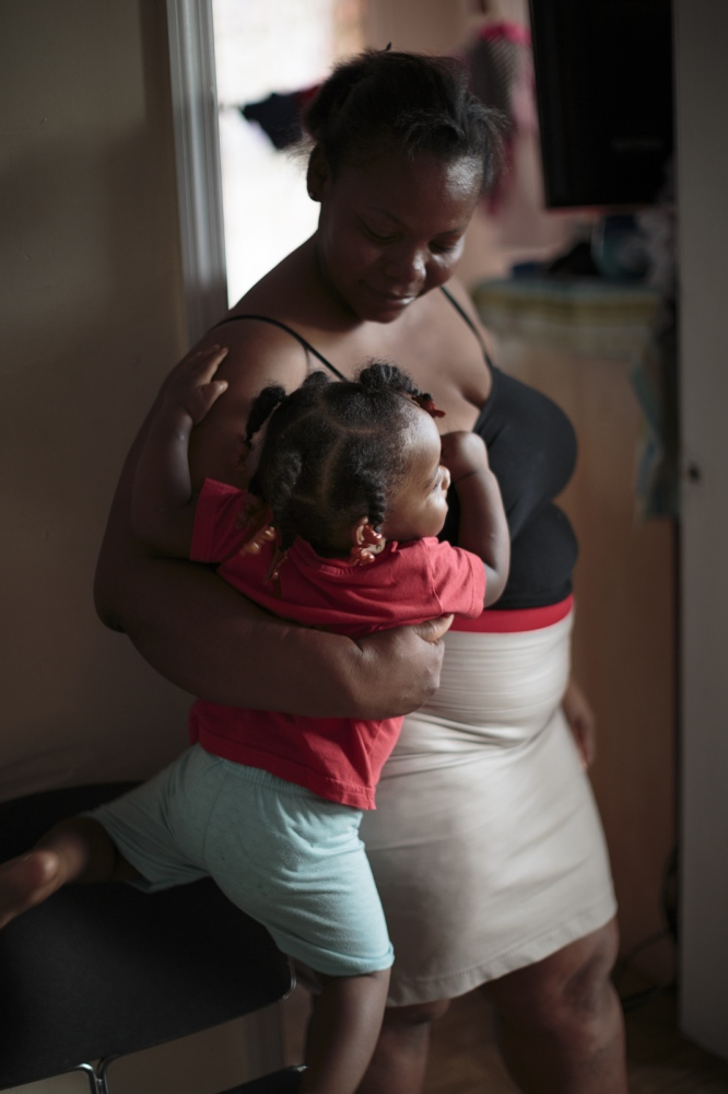 Iselma Mejia holds her daughter Michelle in the living room of their apartment in the South Bronx. Michelle is the youngest of six and at her young age she has inherited the garifuna rhythm and performs the traditional dances with her older sisters at every family celebration.