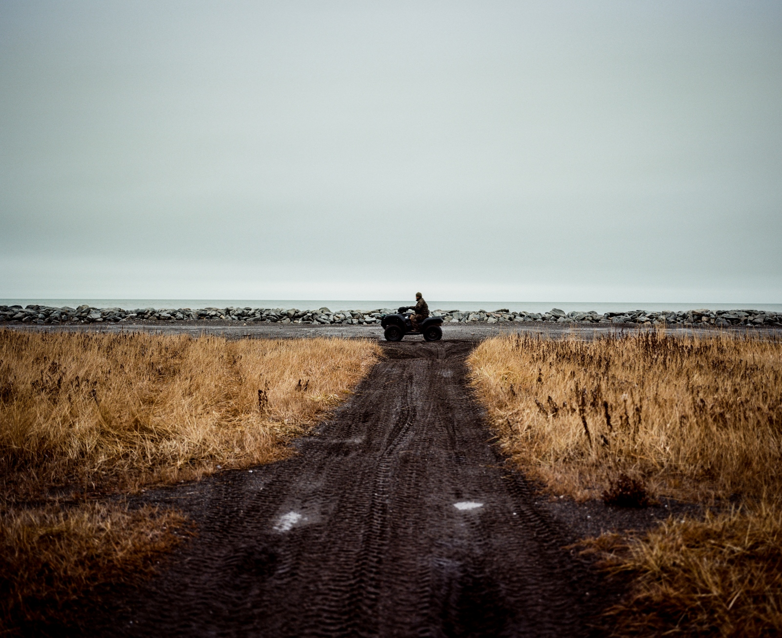 A four-wheeler drives along the sea wall in Kivalina. Because Kivalina is not accessible by road, the most common form of transportation in and around the village is on four wheelers and snow machines.