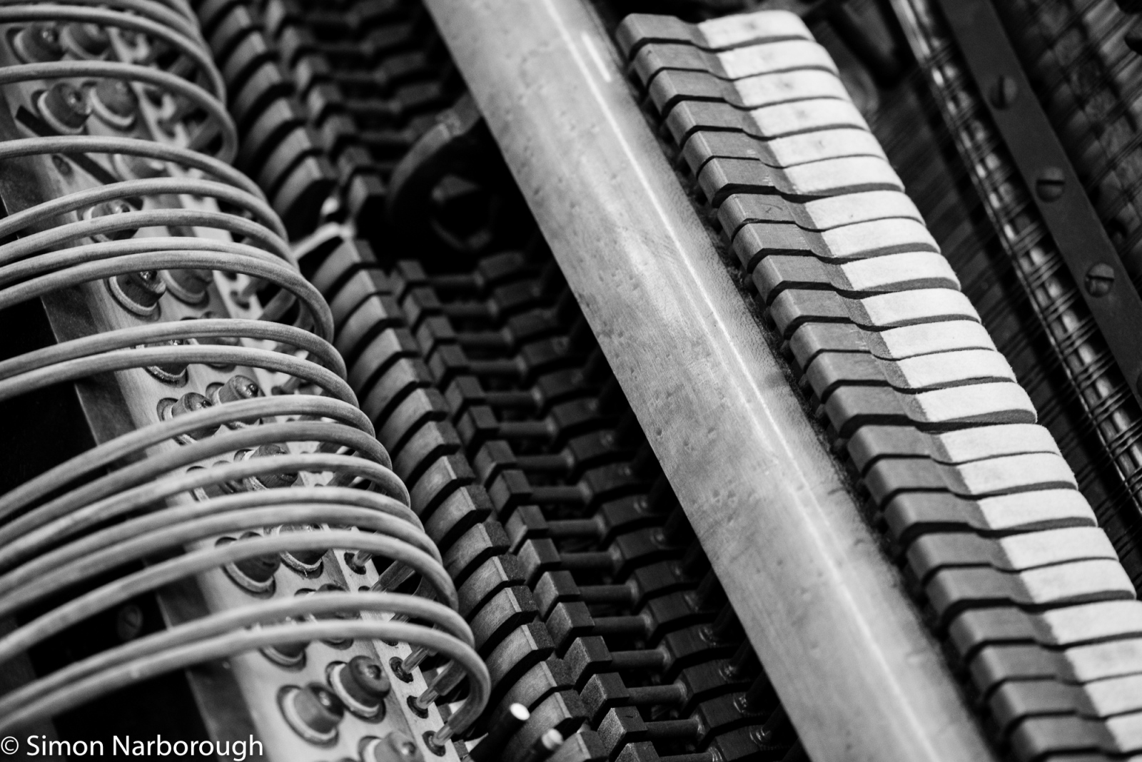 The inner workings of a player piano: a spaghetti-like mass of airtubes, strings and pumps.