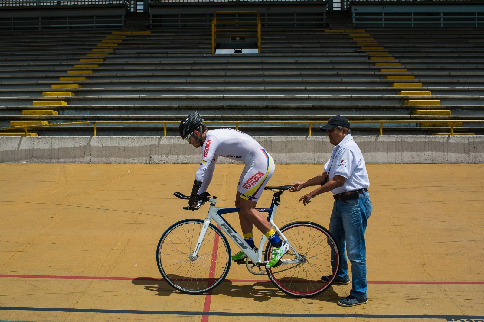 Edwin Matiz, 23, gets ready to start the counter clock training, while his coach Tulio Comcel holds the bicycle on Salitre Sports Complex, Bogotá, 8th June, 2016.