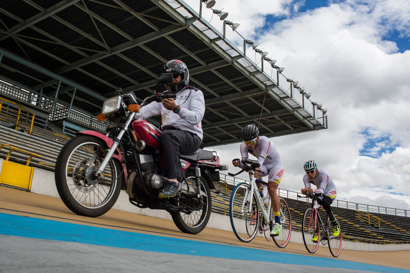 Edwin Matiz, 23, in the middle, chances a motorbike during one of his training sessions at Salitre Sports Complex, Bogotá, 8th June, 2016. Paralympics Cyclists chase the motorbike in order to improve their times on the racetrack.